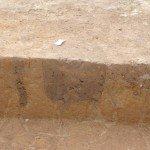 Découvrez ici un trou qui a dû accueillir un poteau en bois.  La différence de couleur de la terre est un des moyens qu'ont les archéologues pour identifier les lieux à explorer.